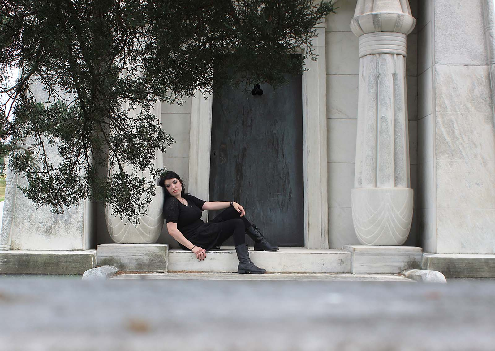 Author looking melancholy and gloomy at a mausoleum in the Laurel Hill Cemetery, dressed in black.
