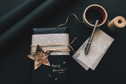 Presents and gifts wrapped in black paper, black tablecloth, star patterned tissue paper and gold accents